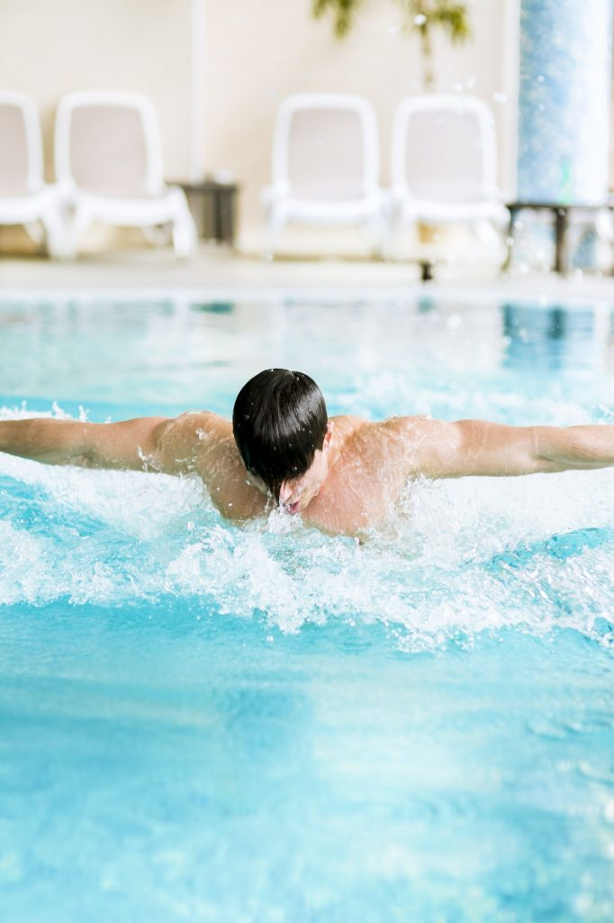 Muscular handsome male swimming in a pool